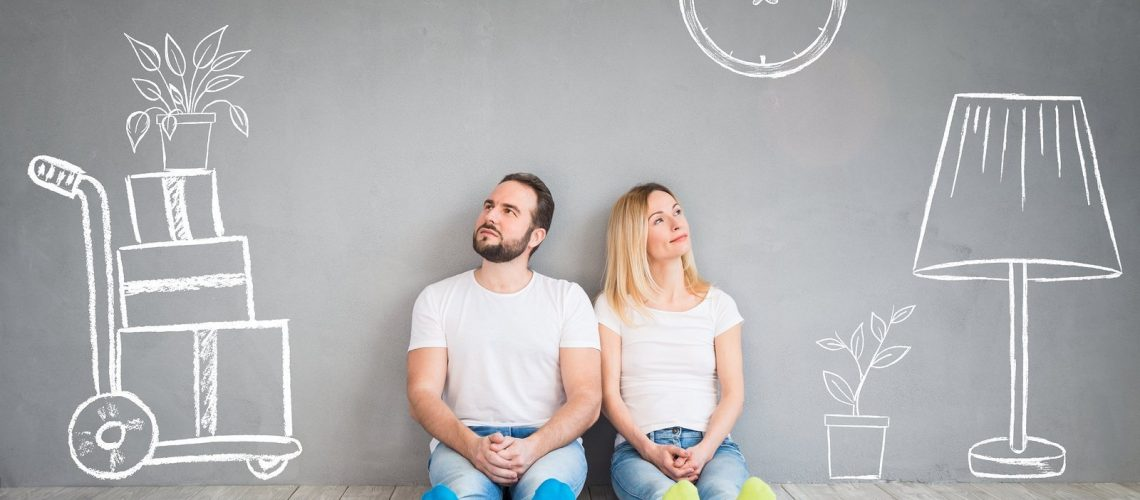 Happy couple sitting on wooden floor. Moving house day new home and design interior concept